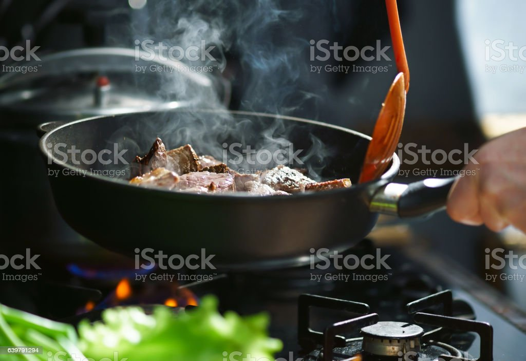 Cooking meat in a frying pan stock photo