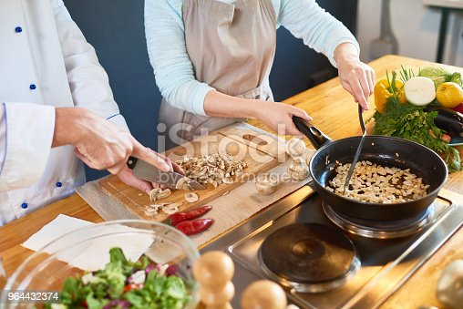 Two cooks cutting and frying mushrooms in the kitchen