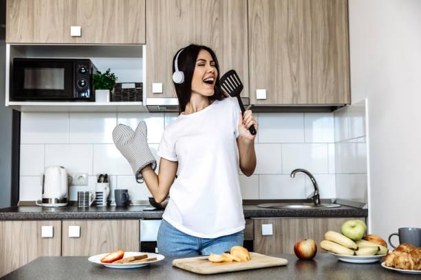 kochen. musik. zuhause. asiatisches mädchen in kopfhörern singt in der küche - promi zuhause stock-fotos und bilder