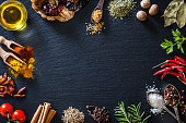 Top view of a black slate background with all sort of spices for cooking and seasoning placed all around the border of an horizontal frame leaving useful copy space for text and/or logo at the center. Spices included in the composition are mustard seeds, oregano, nutmeg, bay leaf, parsley, chili pepper, peppercorns, marine salt, rosemary, cloves, cinnamon sticks, cayenne pepper, paprika and turmeric. A little glass bowl filled with olive oil complete the composition. Low key DSRL studio photo taken with Canon EOS 5D Mk II and Canon EF 100mm f/2.8L Macro IS USM