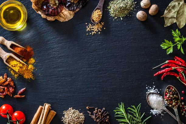 在黑色石板背景上烹調和調味香料邊界 - 材料 個照片及圖片檔