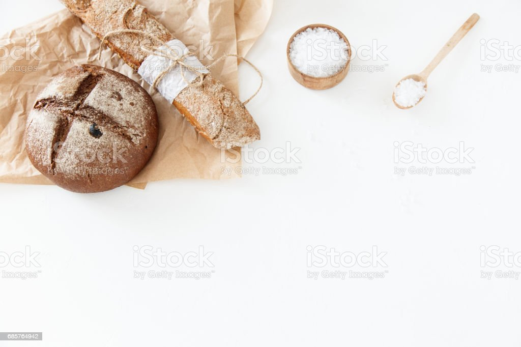 Cooking of homemade bread, black round bread and baguette lie on zbiór zdjęć royalty-free