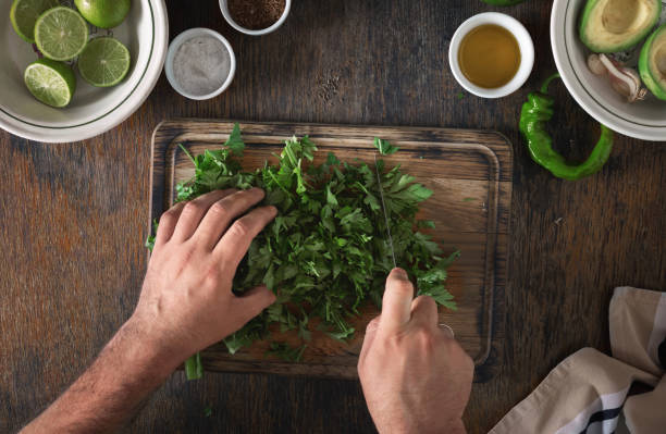 Cooking of Mexican guacamole sauce. Man preparing Mexican sauce guacamole Cooking of Mexican guacamole sauce. Man preparing Mexican sauce guacamole, top view cilantro stock pictures, royalty-free photos & images
