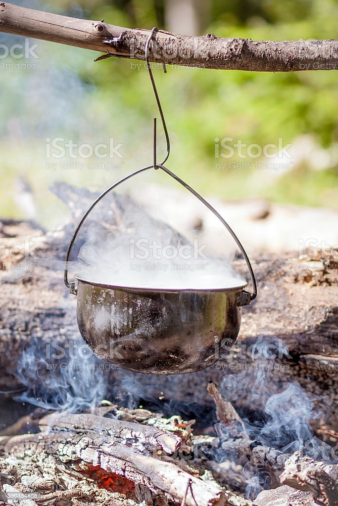 cooking over a campfire in the forest royalty-free stock photo