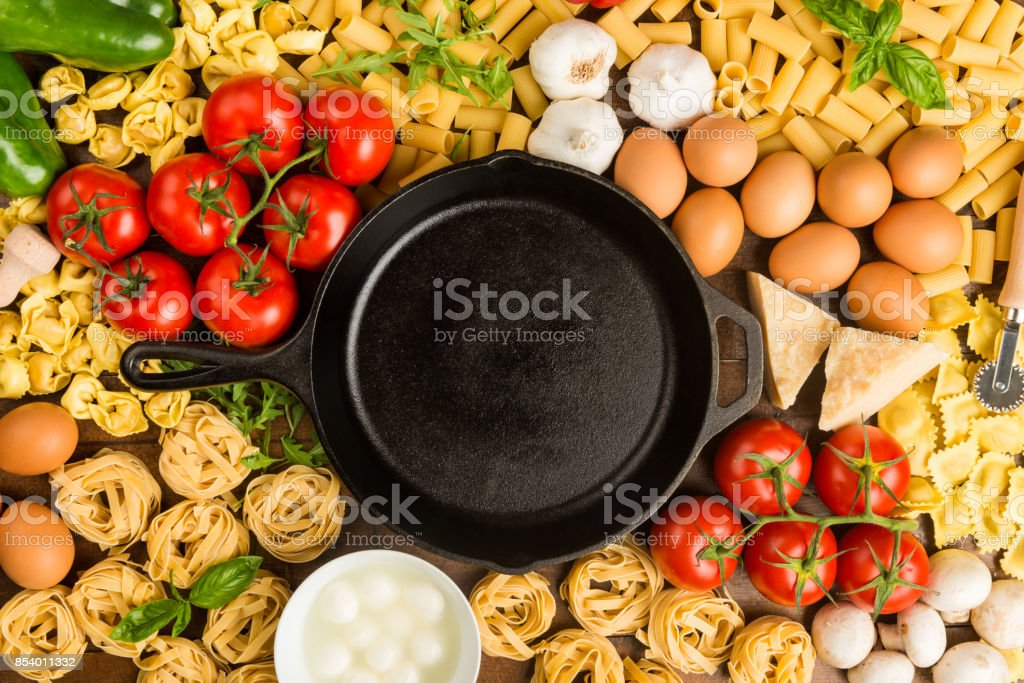 Cooking pan between pasta ingredients royalty-free stock photo