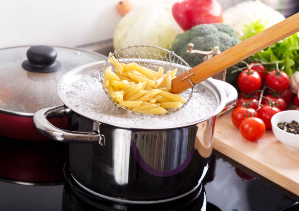 Cooking pasta in a pot with boiling water on a cooker stock photo