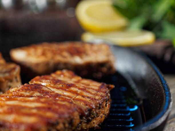 kochen schweinekoteletts - gegrilltes schweinekoteletts stock-fotos und bilder