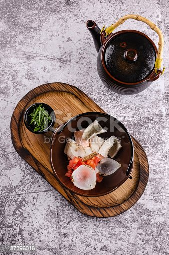Cooking process concept. male hand pouring the broth in Russian traditional fish soup in a bowl - ukha, served with green onions and vodka on on wooden board background. Fish broth in a teapot. traditional, national cuisine in Russia.