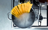 Cooking raw spaghetti in the boiling water contained in a saucepan. Italian cuisine. Raw food. interior of a domestic kitchen. Food preparation and cooking