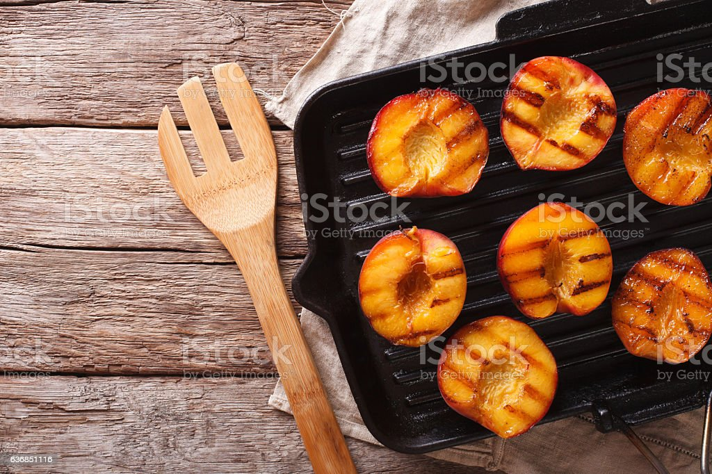Cooking Ripe peaches on a grill pan close-up. horizontal stock photo