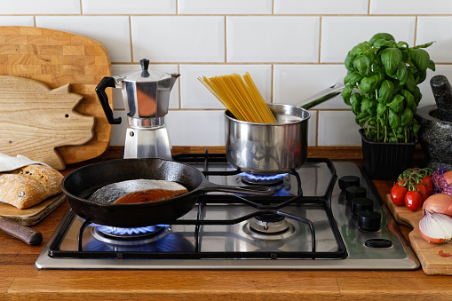 Cooking salmon fillet with skin and spaghetti on a gas stove in traditional home kitchen. Wood worktop.