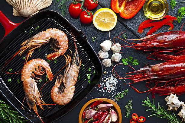 cooking shrimps in a grill - gegrillte garnelen stock-fotos und bilder