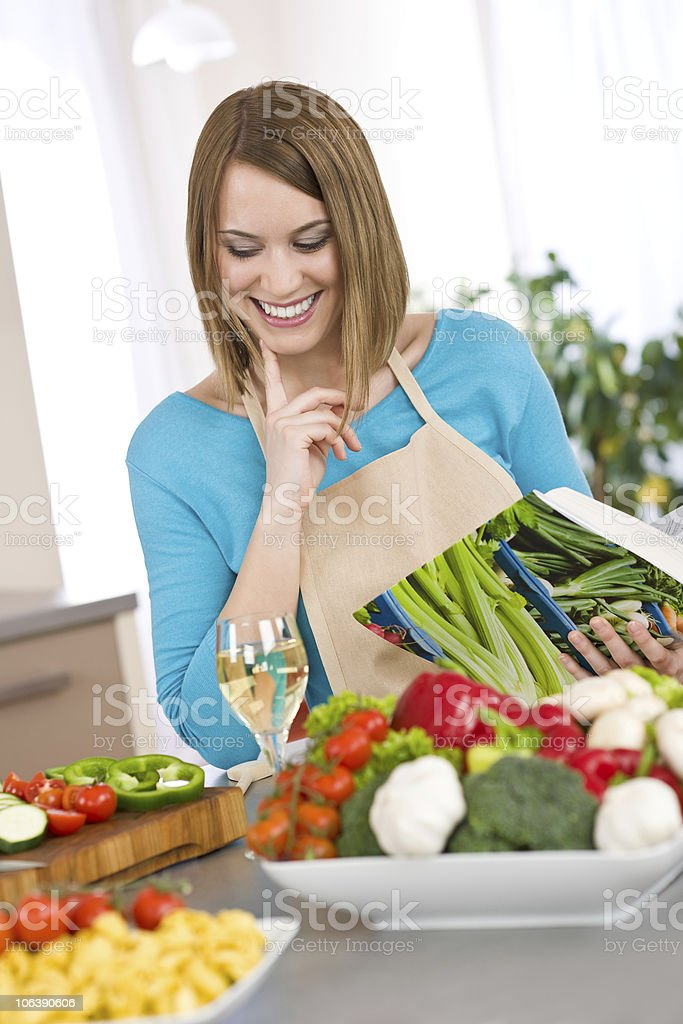 Cooking - Smiling woman holding cookbook, with vegetable and pasta royalty-free stock photo
