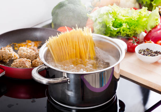 Cooking spaghetti in a pot with boiling water stock photo