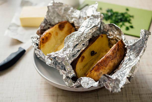 cooking stuffed baked potato - alufolie backofen stock-fotos und bilder