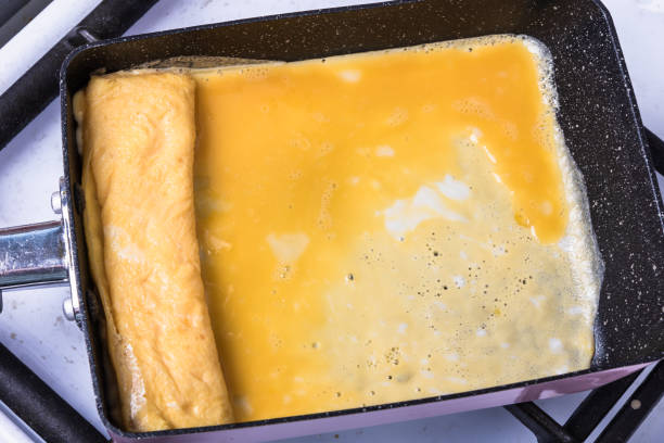 Cozinhando omelete japonesa tamago em uma panela especial para tamagoyaki. - foto de acervo