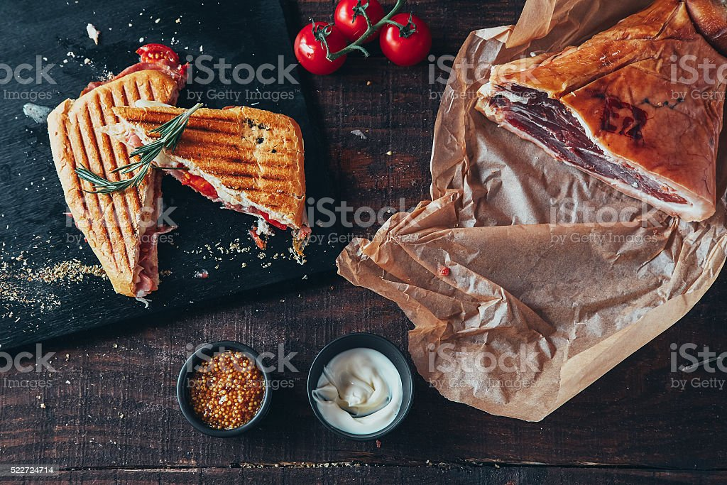 cooking tasty panini with ham covered with cheese, tomatoes stock photo