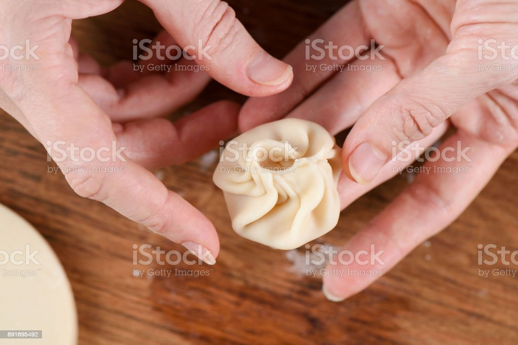 Cooking techniques. Closeup of woman hands making purse shape dumpling momo stock photo