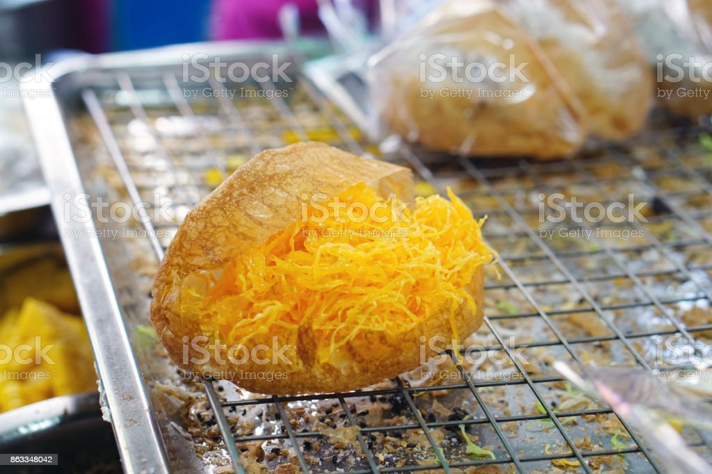 Cooking Thai coconut pancake in pan (Khanom thang taek) topped with sweet egg floss, Most famous of Thai dessert, Street food in Thailand. stock photo
