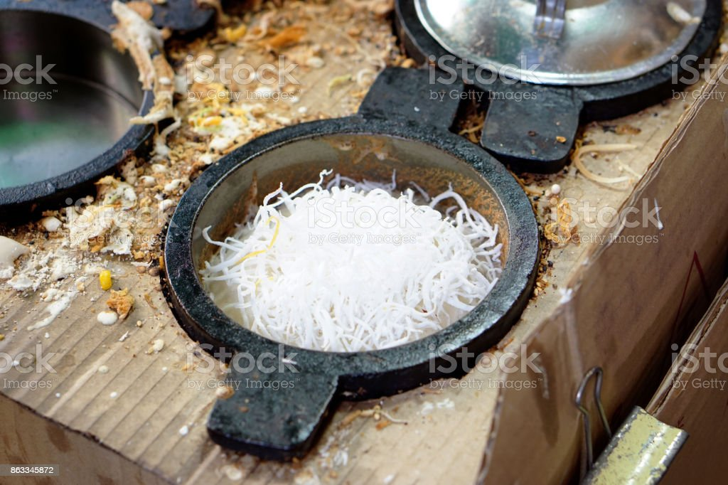 Cooking Thai coconut pancake in pan (Khanom thang taek) topped with sweet shredded coconut and sugar, Most famous of Thai dessert. stock photo
