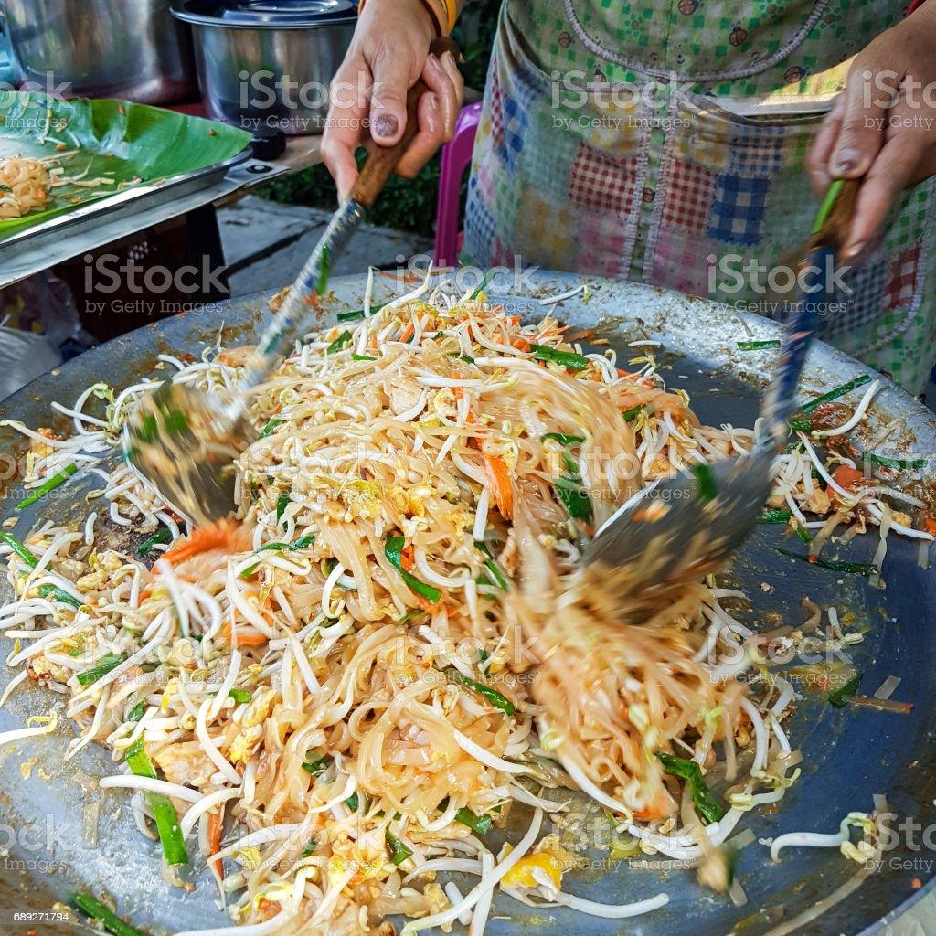 薄いオムレツで包んだ「パッタイ」麺もやし、鶏肉か海老と野菜の炒め揚げ料理であると呼ばれる有名なタイ屋台料理料理を調理。 ストックフォト