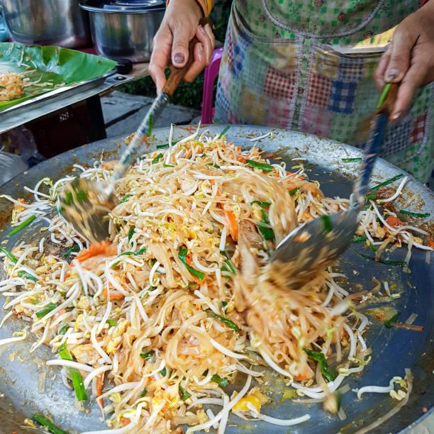 薄いオムレツで包んだ「パッタイ」麺もやし、鶏肉か海老と野菜の炒め揚げ料理であると呼ばれる有名なタイ屋台料理料理を調理。 - タイ料理 ストックフォトと画像