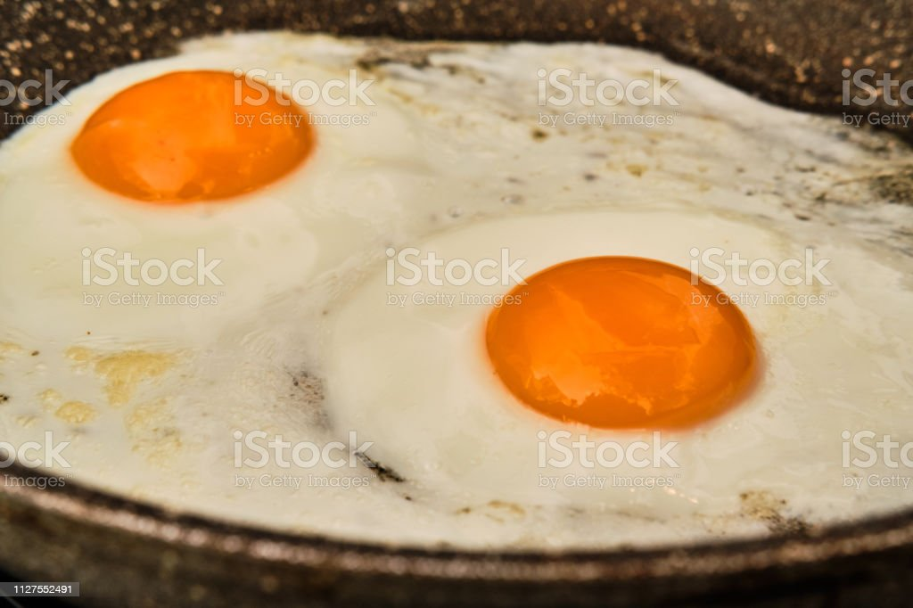 Cooking two fryed egg on frying pan