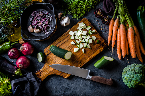 Top view of a wooden cutting board with chopped zucchini on top surrounded by vegan ingredients like carrots, onion, broccoli, eggplants, basil, garlic, olive oil, rosemary and a bell pepper. The cutting board is at the center of the image and it is on a grey kitchen tabletop. Low key DSLR photo taken with Canon EOS 6D Mark II and Canon EF 24-105 mm f/4L