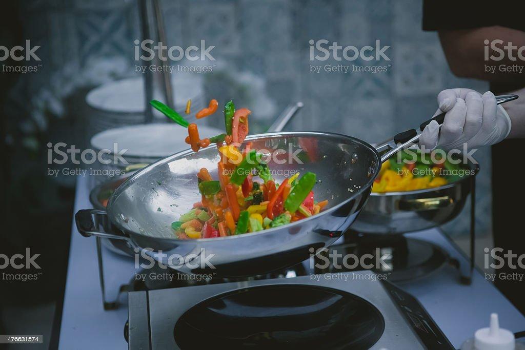 cooking vegetables in wok pan stock photo