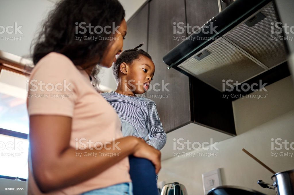 Cooking while taking care of kids is a skill stock photo