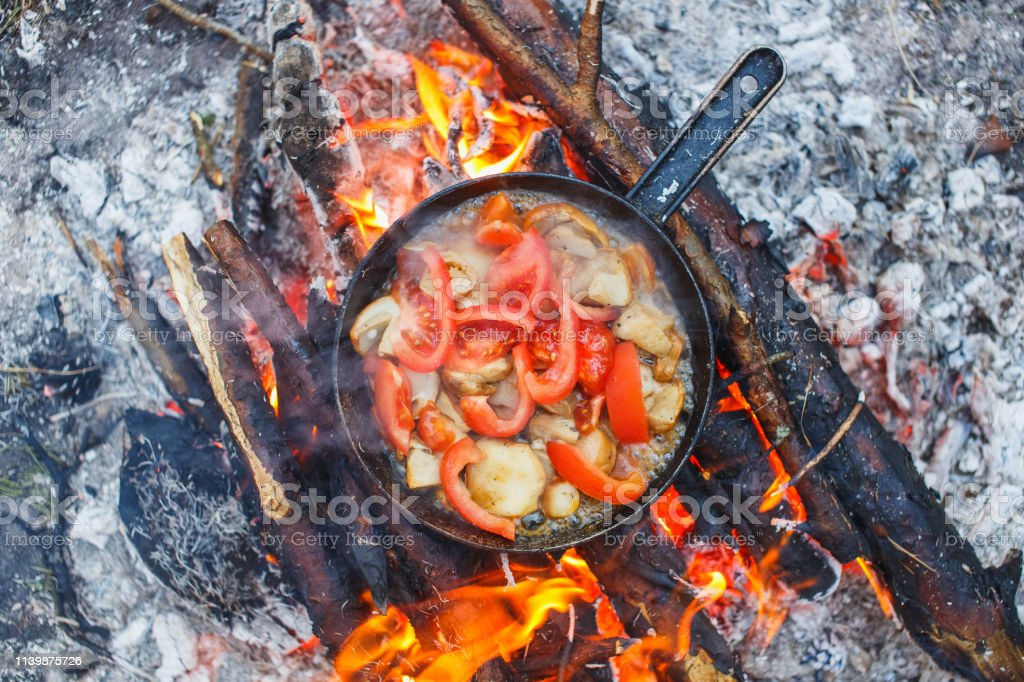Cooking white mushrooms with tomatoes in a pan on a fire in the...