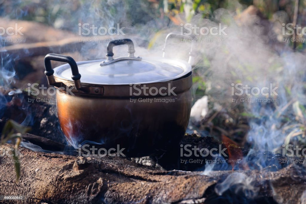 Cooking with cauldron on campfire. stock photo