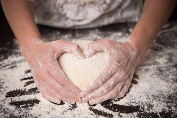 cooking with love. female hands holding dough in heart shape - kneading stock pictures, royalty-free photos & images