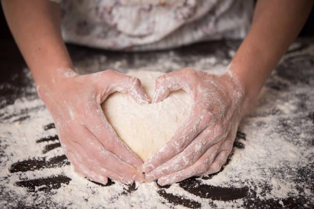 cooking with love. female hands holding dough in heart shape - impastare foto e immagini stock