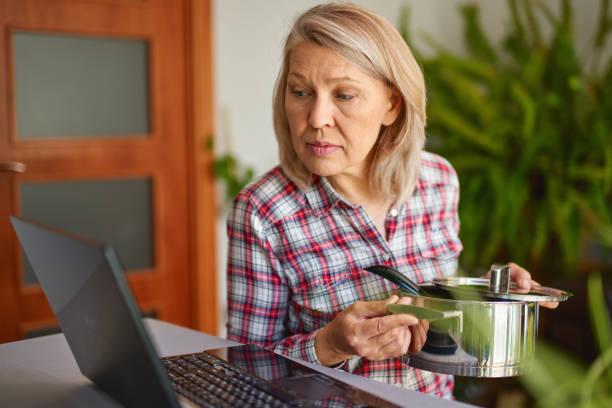 Mujer de cocina mirando la computadora mientras prepara bañaba comida en la cocina. Hermosa mujer madura leyendo receta de cocina - foto de stock