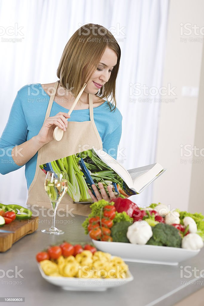 Cooking - Woman reading cookbook in kitchen with vegetable royalty-free stock photo