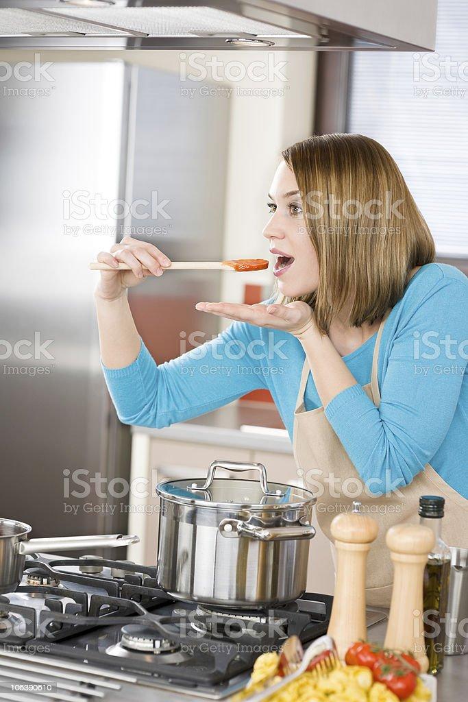 Cooking - Woman tasting Italian tomato sauce in modern kitchen royalty-free stock photo