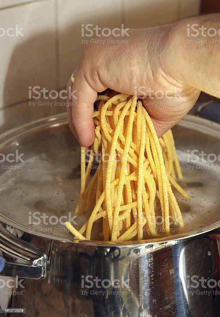 Cook mano e gettano in acqua bollente spaghetti fatti in casa - foto stock