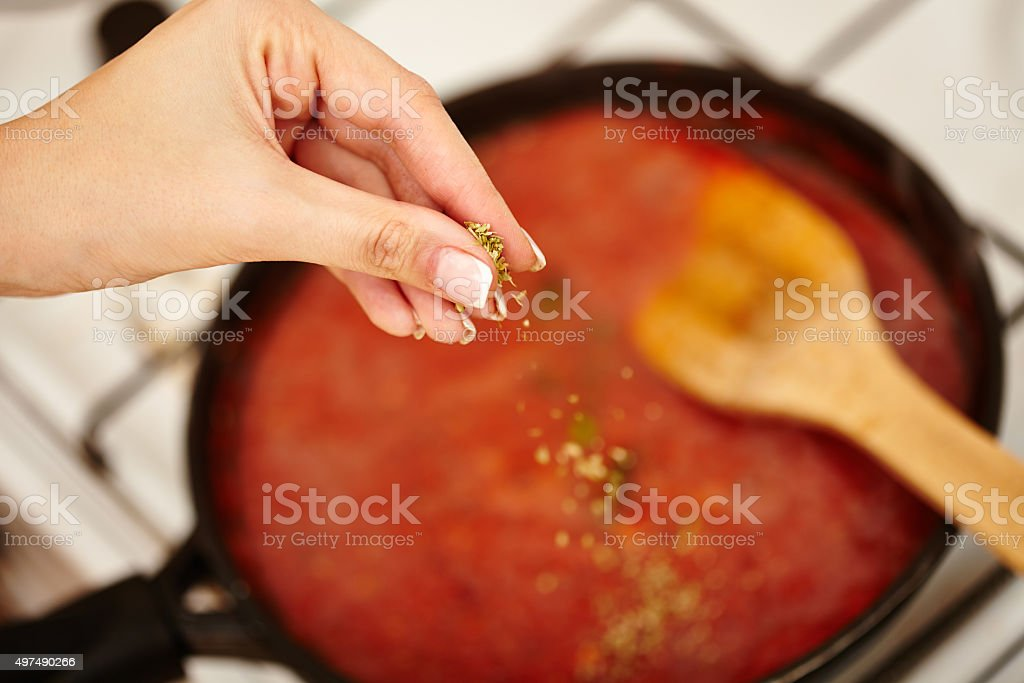 Cook's hand sprinkling parsley and basil in the sauce pan stock photo