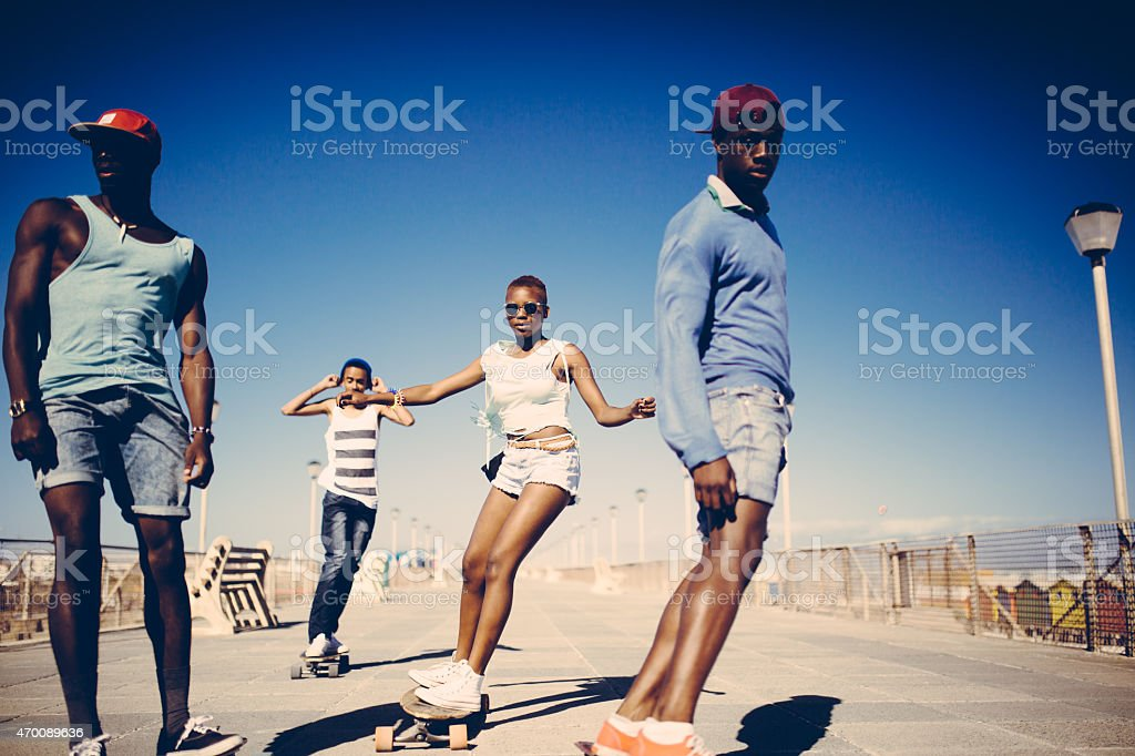 Cool African American teenagers longboarding at the beach stock photo