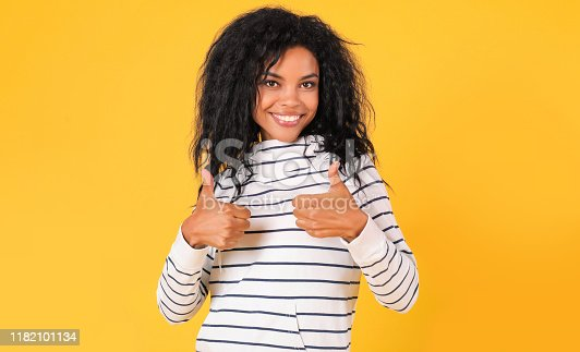 857924506 istock photo Cool! African Ethnic woman in white striped hoodie is posing on a yellow background, showing thumbs up, looking at the camera and smiling joyfully. 1182101134