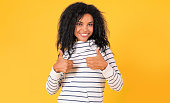 istock Cool! African Ethnic woman in white striped hoodie is posing on a yellow background, showing thumbs up, looking at the camera and smiling joyfully. 1182101134