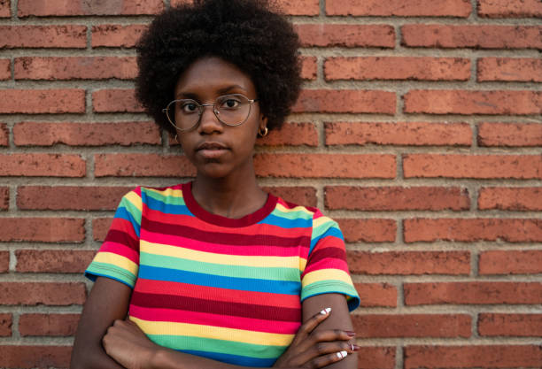 Cool african girl by brick wall stock photo