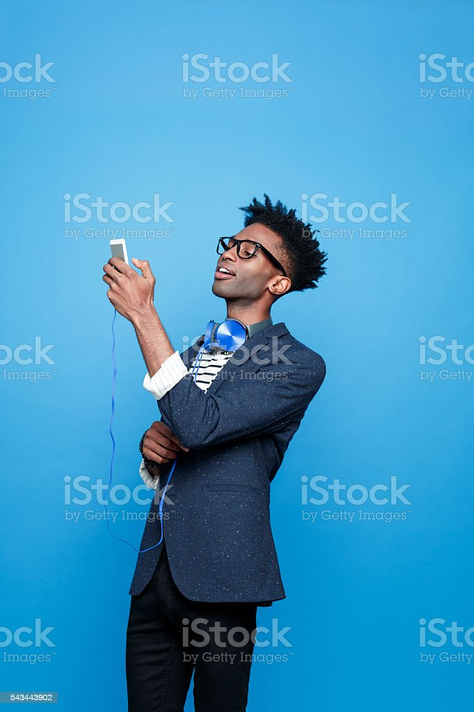 Cool afro american guy using a smart phone Studio portrait of fashionable afro american young man wearing striped top, navy blue jacket, nerd glasses and headphone, using a smart phone. Studio portrait, blue background. Adult Stock Photo