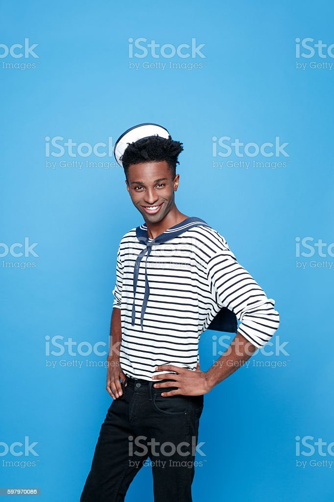 Cool afro american young sailor Portrait of happy afro american young man in sailor style outfit, smiling at camera with hands on hips. Studio portrait, blue background. Adult Stock Photo
