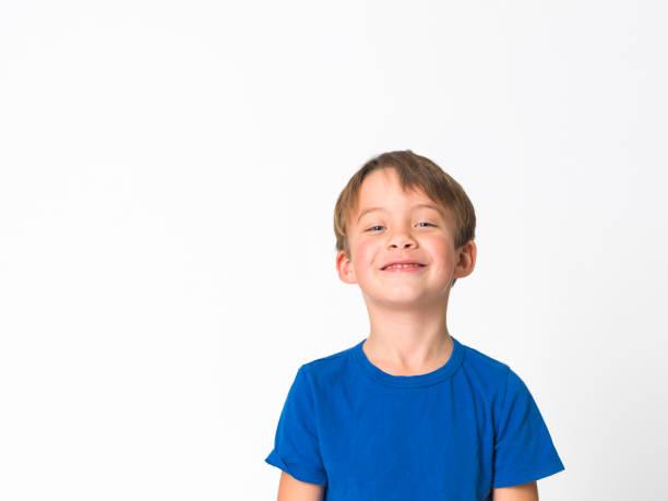 Cooler und niedlicher sechsjähriger Junge in roter Hose und blauem Hemd posiert vor weißem Hintergrund – Foto