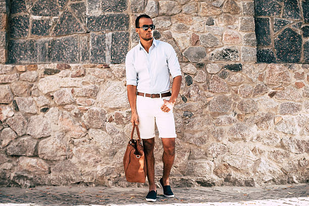 Cool and in style. Full length of handsome young African man in smart casual clothes carrying bag and looking away while standing against the stoned wall outdoors shorts stock pictures, royalty-free photos & images