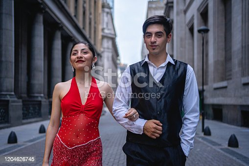 Beautiful young and elegant dancing couple on the street of a city.