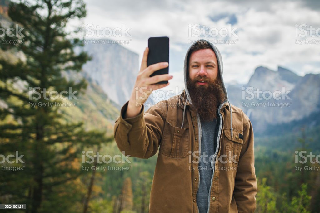 cool bearded man taking selfie photo with smartphone royalty-free stock photo
