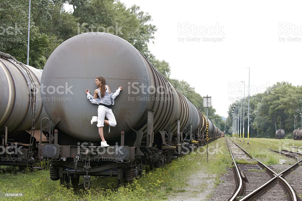 cool, beautiful woman on a oil storage tank royalty-free stock photo
